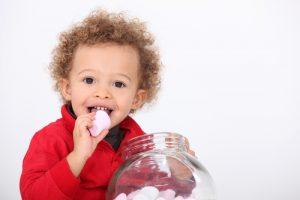 A cute kid eating marshmallow