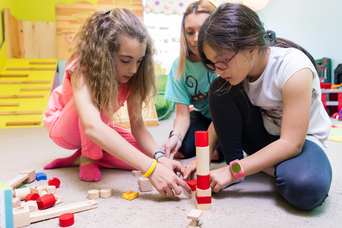 Two girls playing together with wooden toy blocks