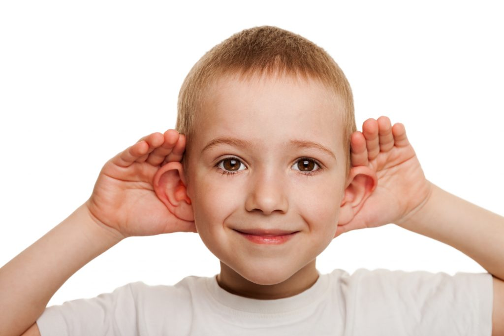 boy holding ears