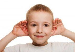 boy holding ears