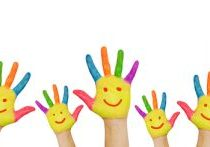Children's smiling colorful hands raised up.