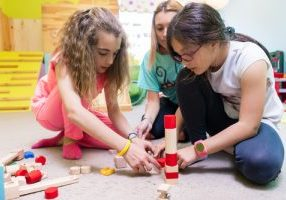 Two girls playing together with wooden toy blocks on the floor d