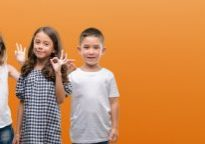 Group of boy and girls kids over orange background doing ok sign with fingers, excellent symbol